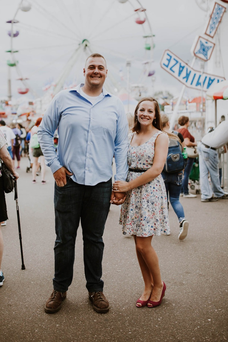 holding_hands_smiling_at_camera_ferris_wheel_fair_engagement.jpg