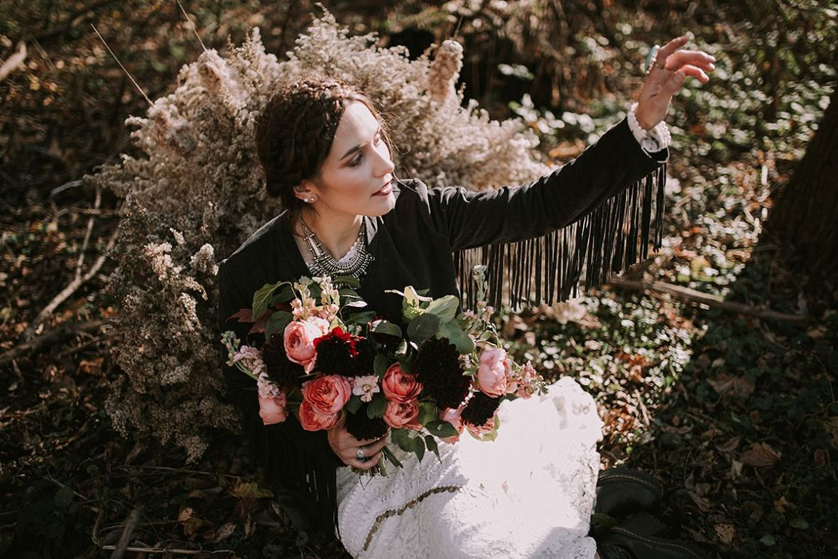 holding_up_arm_black_fringe_leather_jacket_over_wedding_gown.jpg
