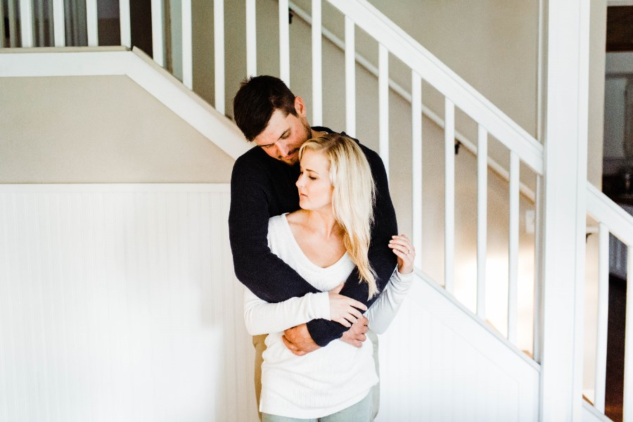 in_home_engagement_session_standing_by_white_stairs.jpg