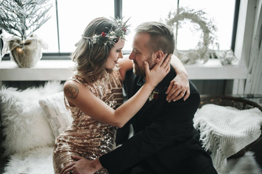 intimate_winter_boho_bride_and_groom_embrace_on_white_fur_couch.jpg