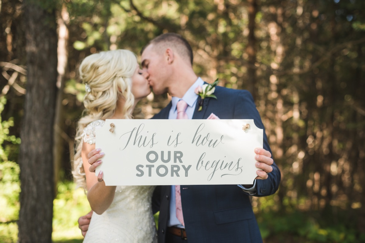kissing_newlyweds_holding_up_this_is_how_our_story_begins_sign.jpg