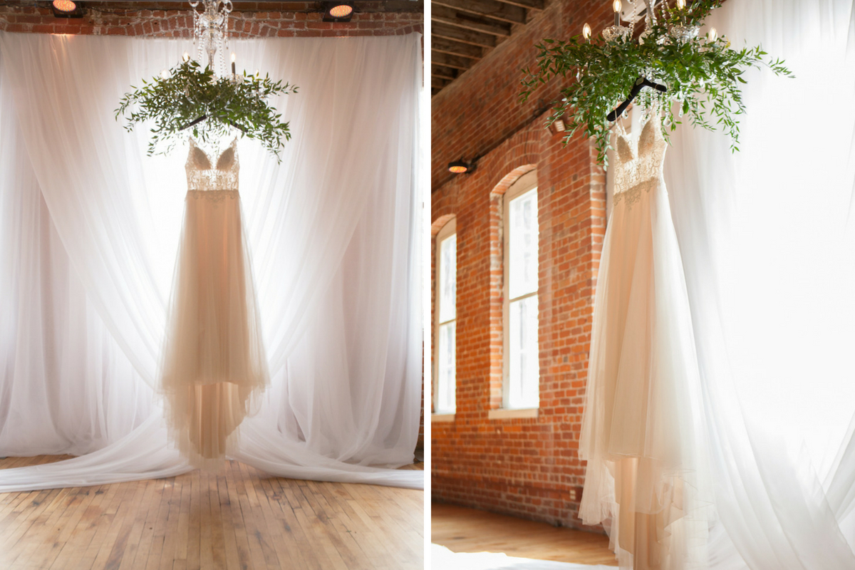 lace_wedding_gown_hanging_by_bright_window_brick_walls.jpg