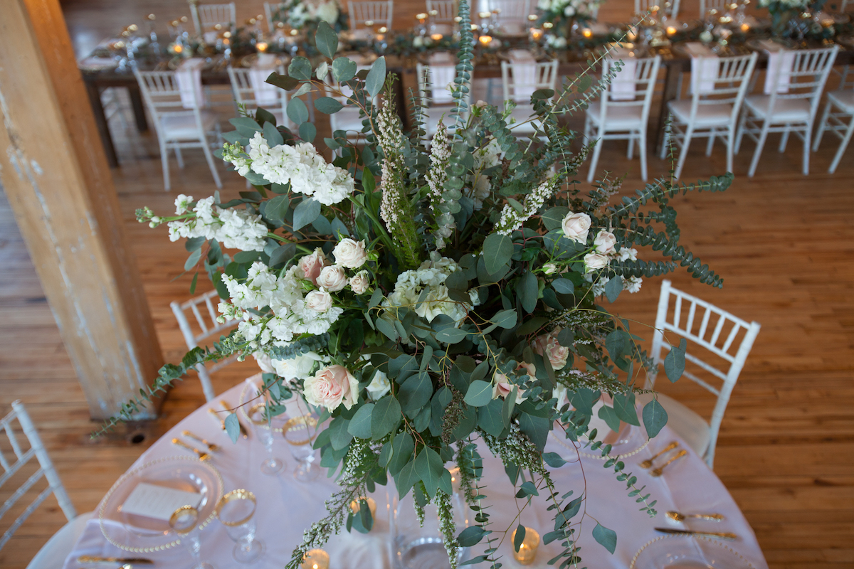 large_green_floral_wedding_table_centerpiece_wood_floors.jpg