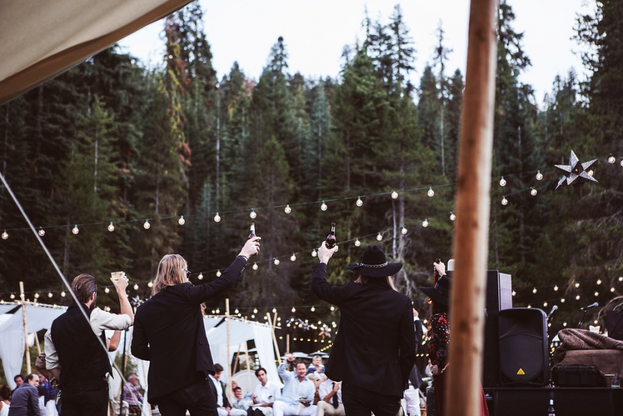 live_band_playing_at_outdoor_wedding_reception_with_string_lights_raising_beer_glasses.jpg