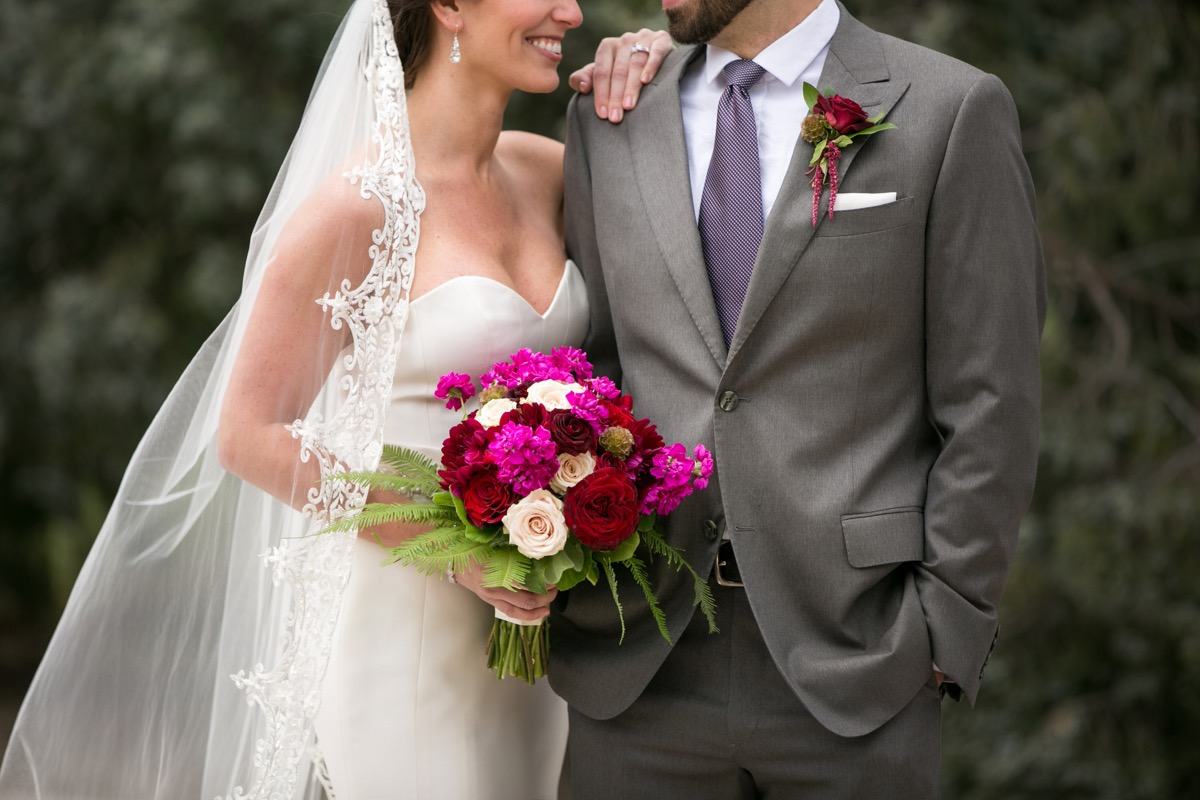 long_bridal_veil_with_lace_trimming_bright_pink_red_bouquet_simple_strapless_gown.jpg