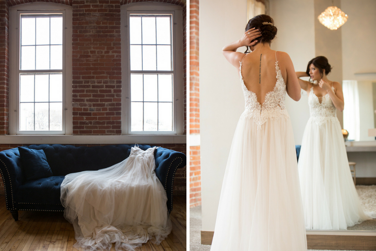 long_wedding_gown_laying_across_navy_blue_felt_couch.jpg