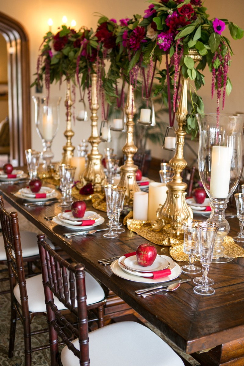 long_wooden_reception_table_romantic_pink_flowers_greenery_hanging_above_table_giant_gold_candle_holders_apple_seating_cards.jpg