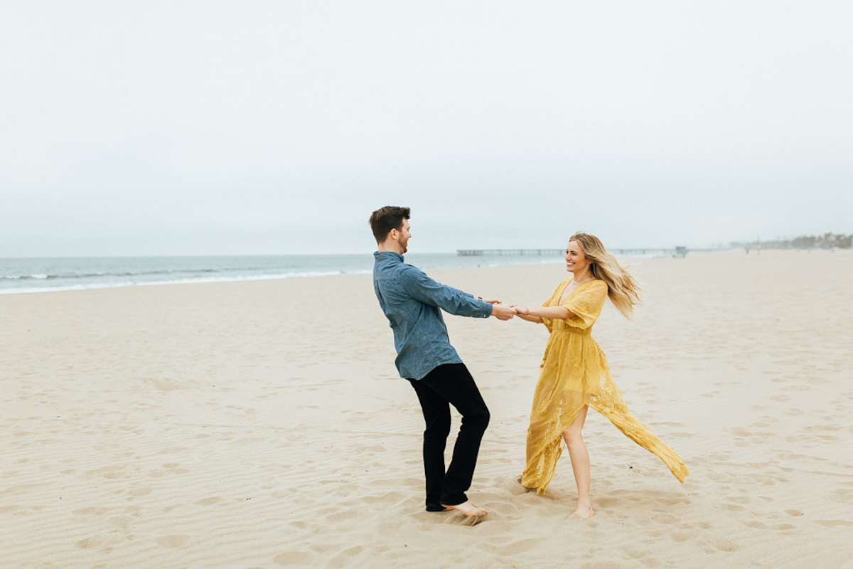 man_and_woman_in_yellow_dress_twirling_on_california_beach.JPG