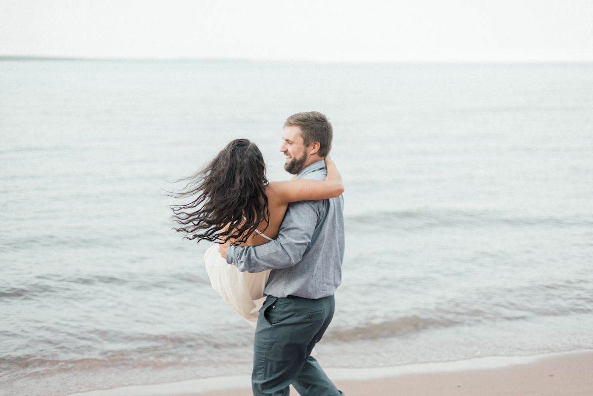 man_carrying_fiance_in_arms_on_calm_beach_water_in_background.jpg