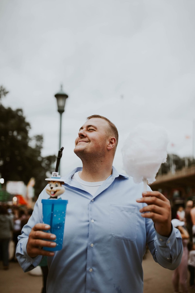 man_engagement_photos_state_fair_holding_cotton_candy.jpg