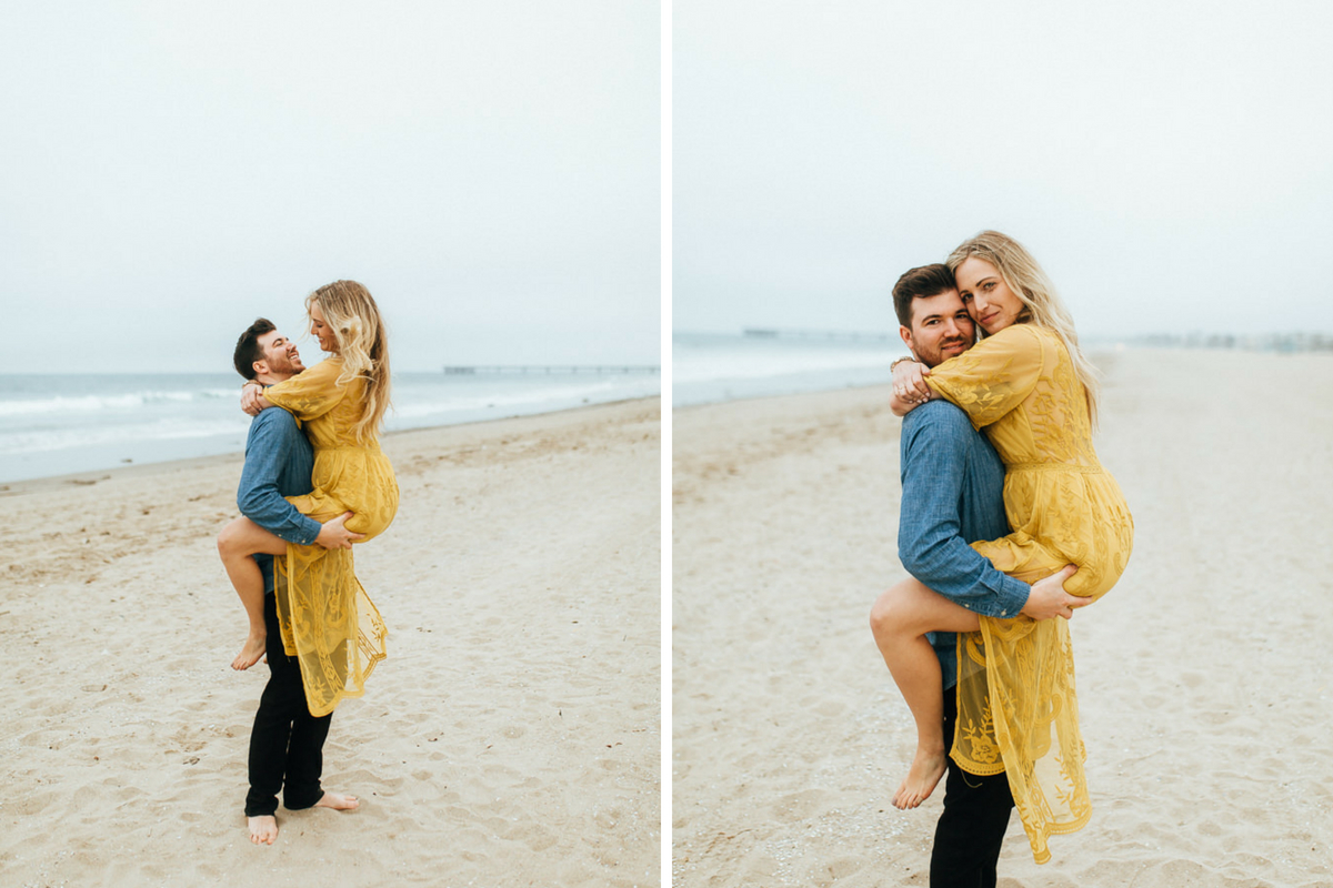 man_holding_fiance_bright_yellow_dress_on_sandy_california_beach.jpg