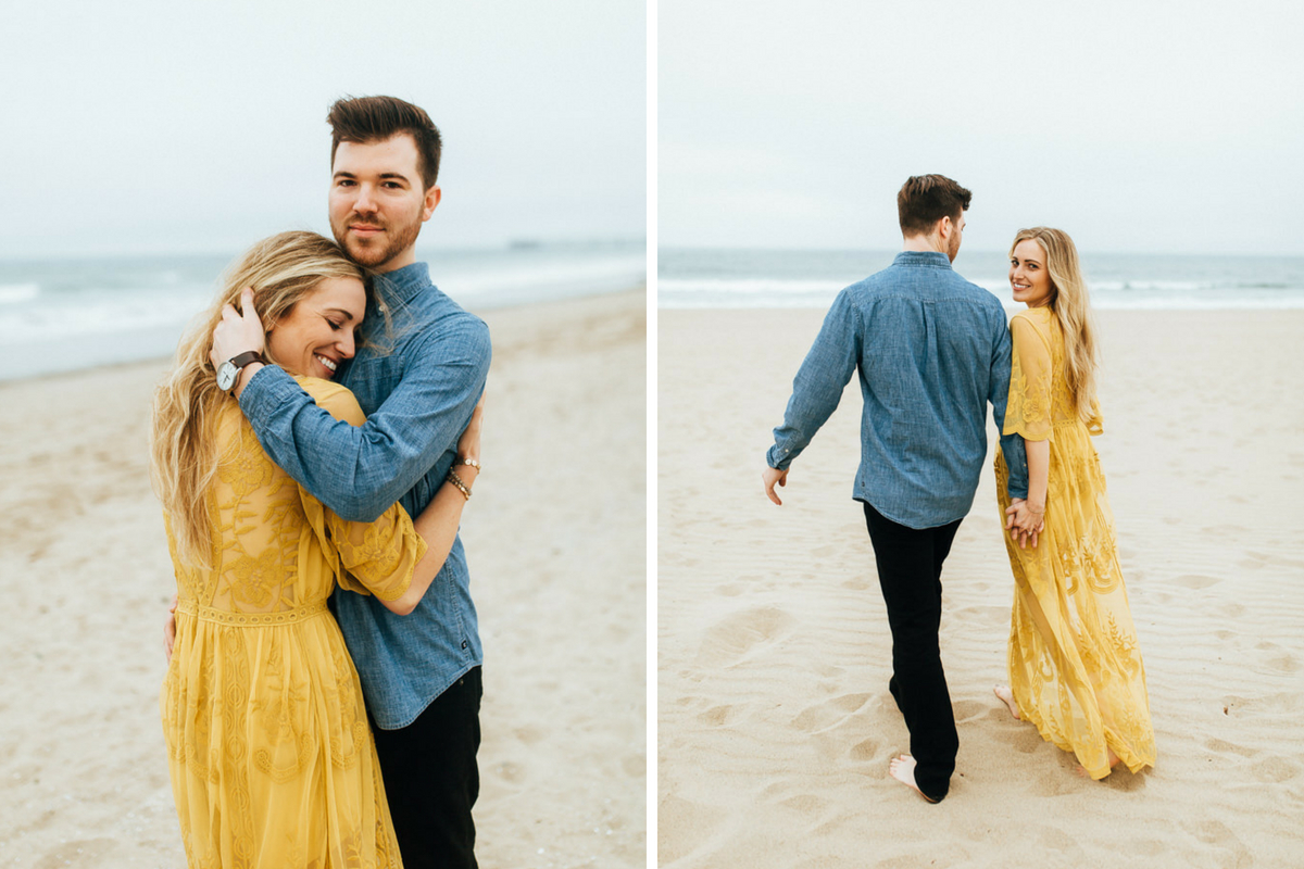 man_holding_fiance_close_to_chest_hand_in_hair_on_california_beach.jpg