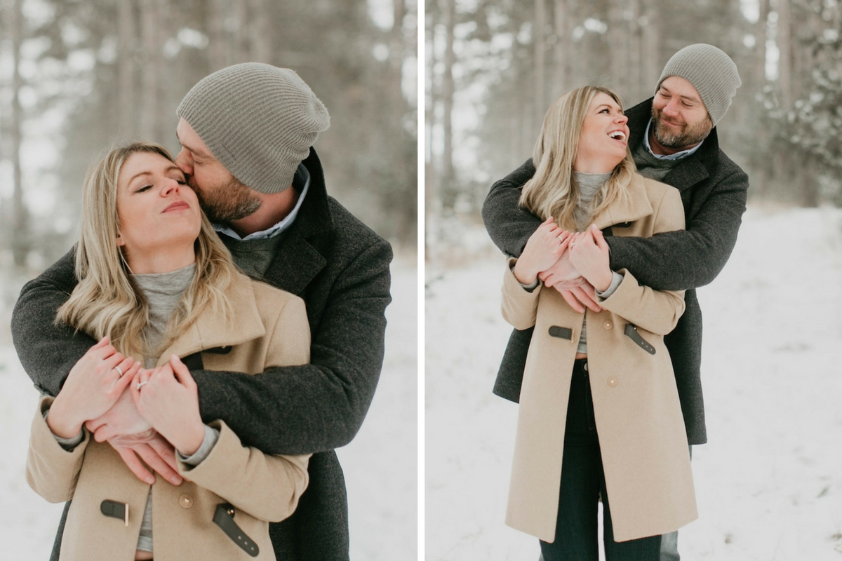 man_hugging_fiance_kissing_cheeck_in_snowy_woods.jpg
