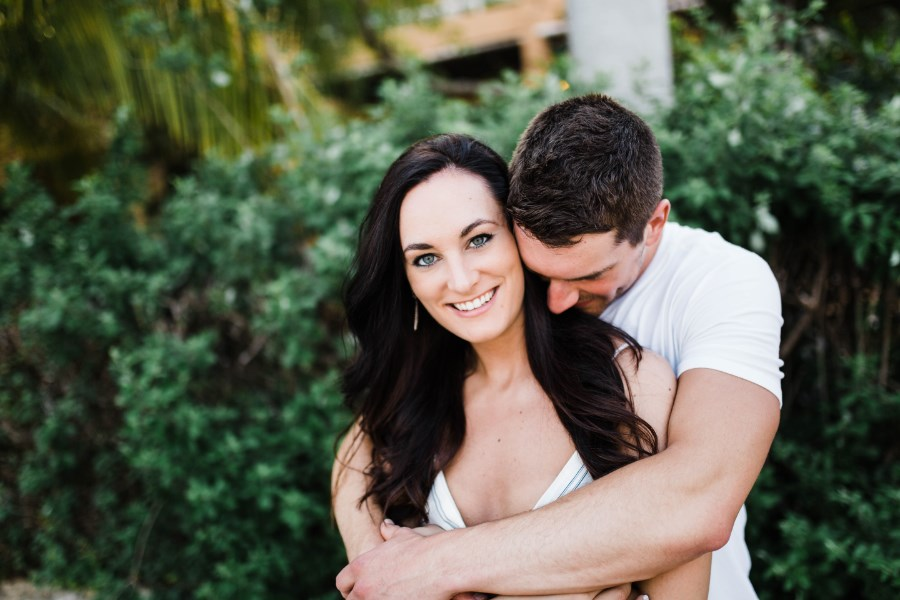 man_hugging_woman_from_behind_palm_tree_engagement_photos.jpg