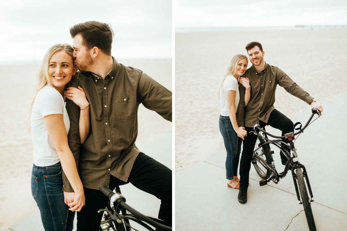 man_kissing_fiances_head_on_bike_at_bright_sandy_beach.jpg