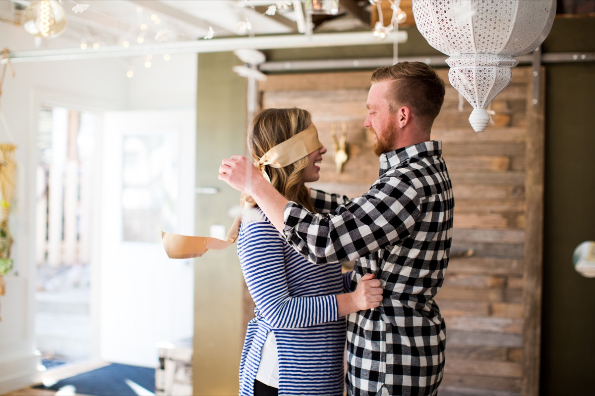 man_taking_off_womens_gold_blindfold_before_proposal.jpg
