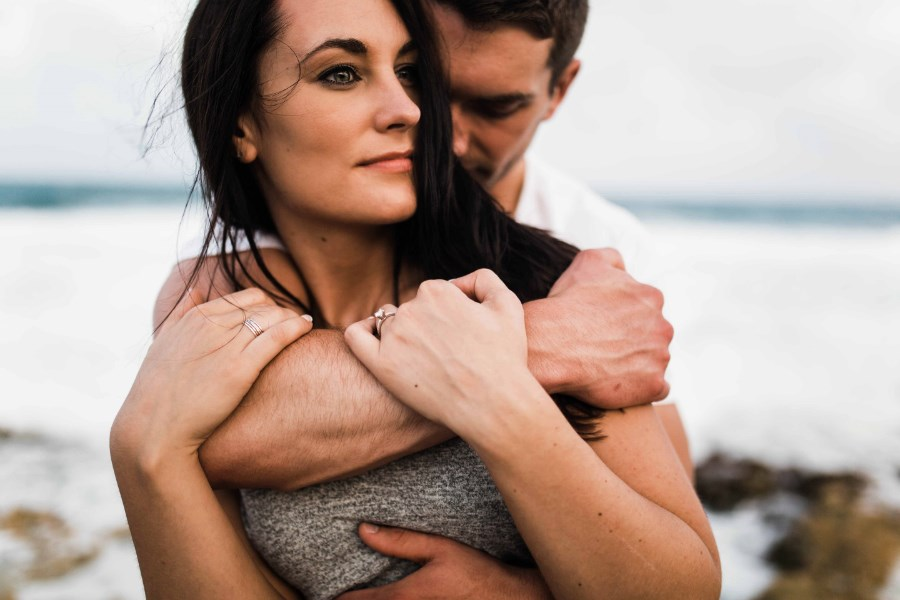 man_wrapping_arm_around_womans_neck_ocean_engagement.jpg