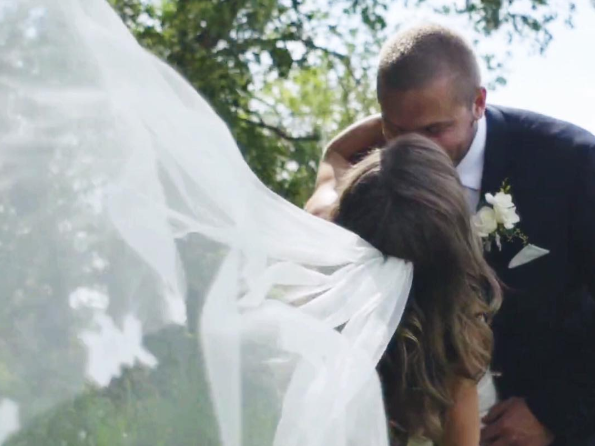 minnesota_wedding_videography_shot_of_long_bridal_veil_blowing_in_the_wind_as_she_kisses_her_groom.png