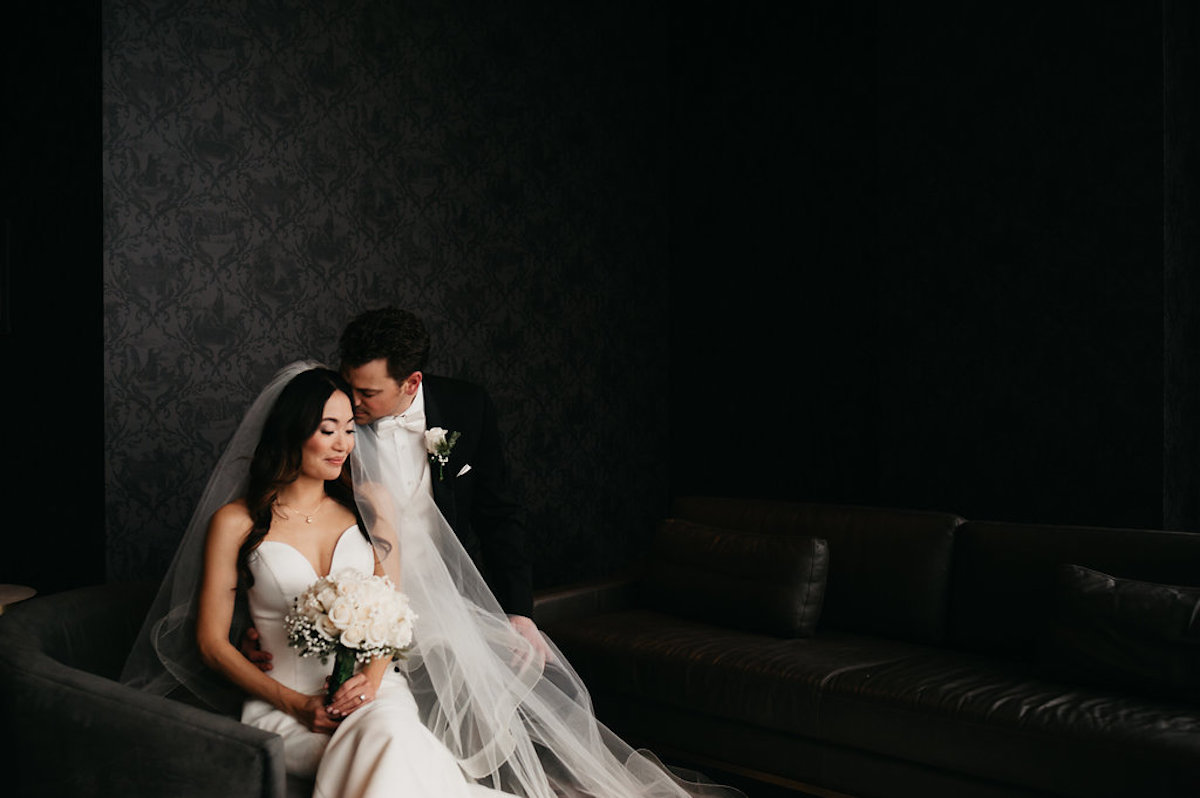 moody_bride_and_groom_sitting_together_embracing_in_black_room.jpg