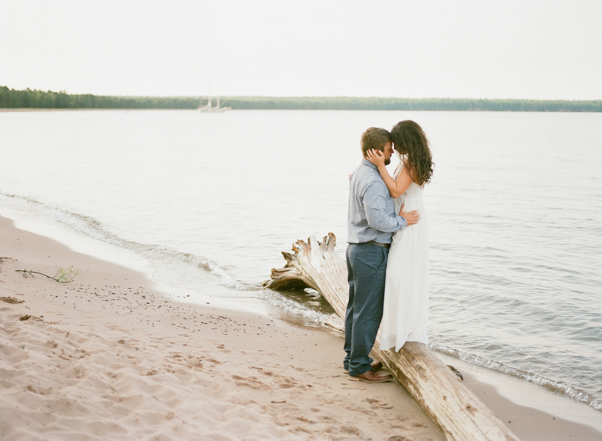 moody_engagement_photo_couple_embracing_on_calm_beach_woman_standing_on_log.jpg