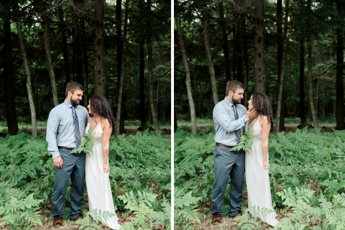 moody_engagement_photo_couple_standing_in_front_of_dark_green_forest.jpg