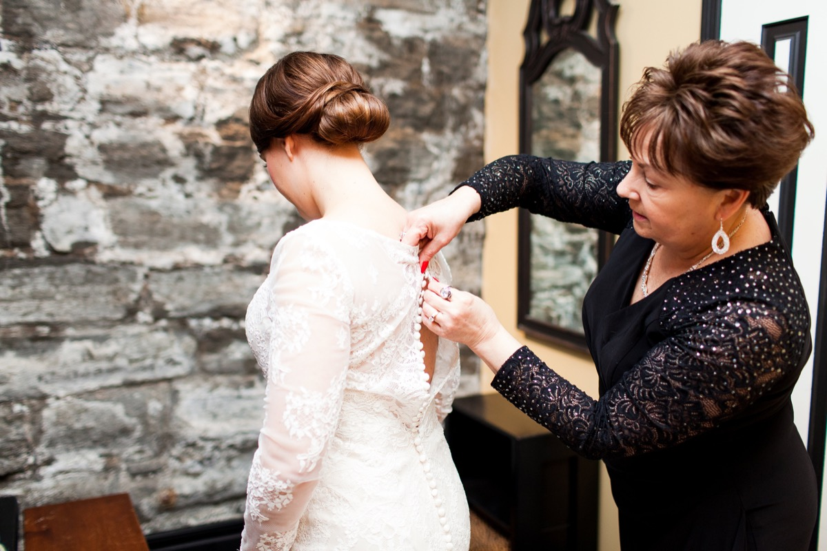 mother_buttoning_brides_lace_gown_red_nails.jpg