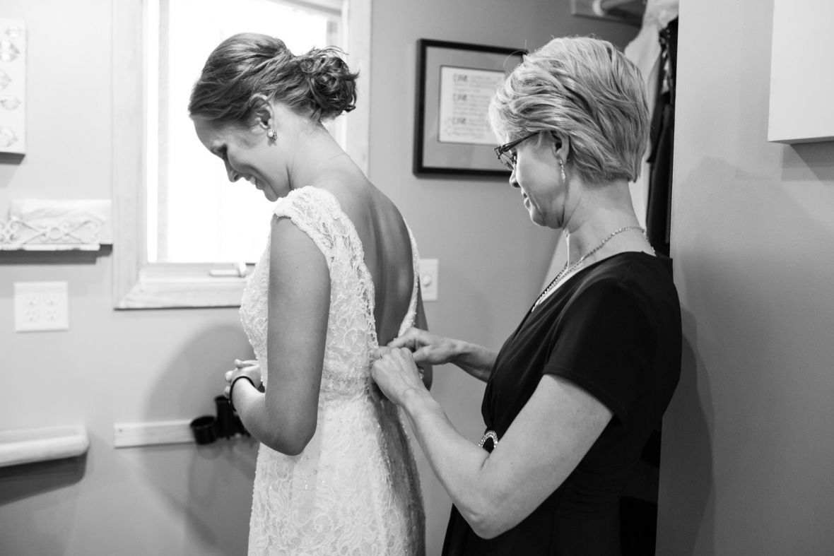 mother_buttoning_up_back_of_brides_lace_wedding_gown.jpg