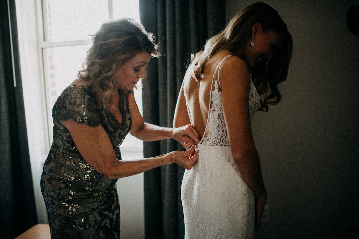 mother_of_bride_buttoning_wedding_gown_bride_smiling.jpg