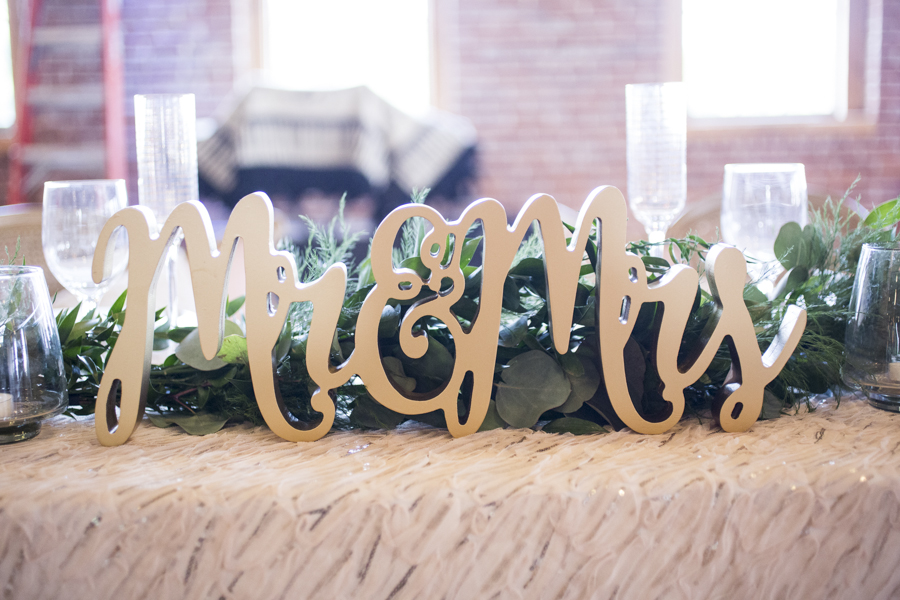 mr_and_mrs_white_wooden_sign_reception_table_greenery.JPG
