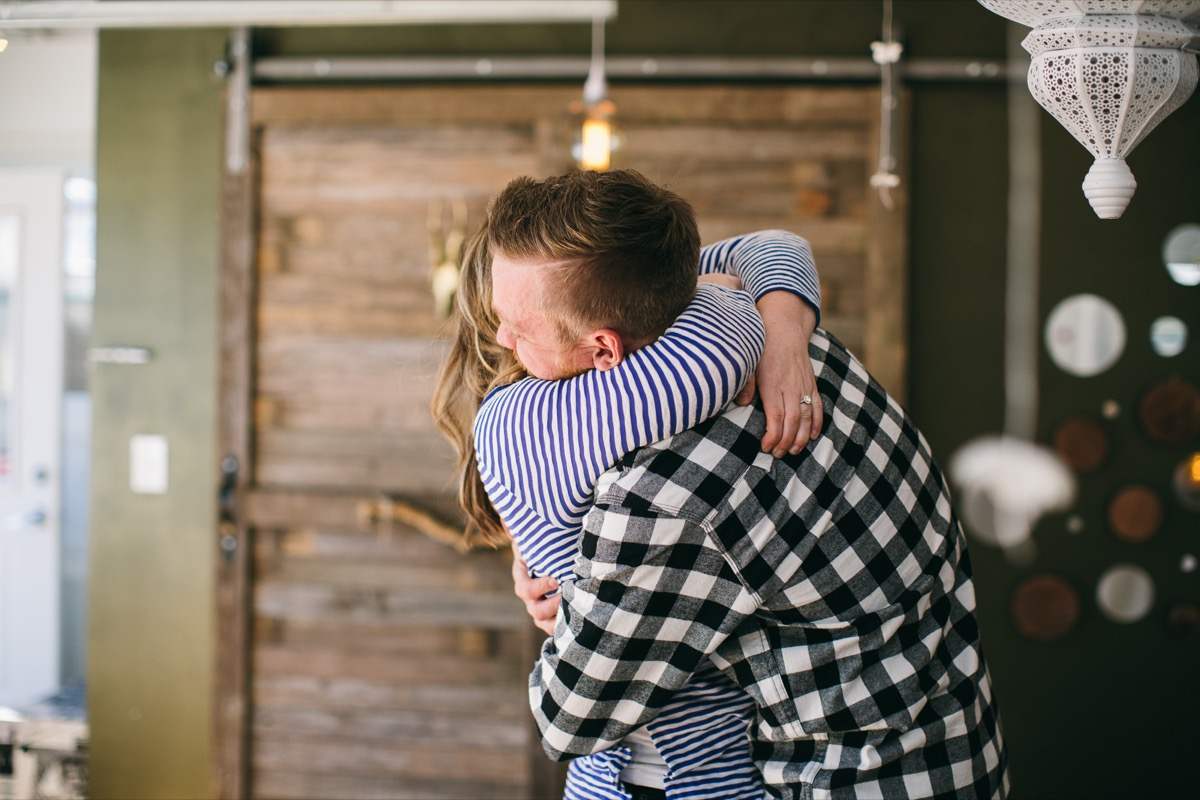 newly_engaged_couple_hugging_in_bungalow.jpg