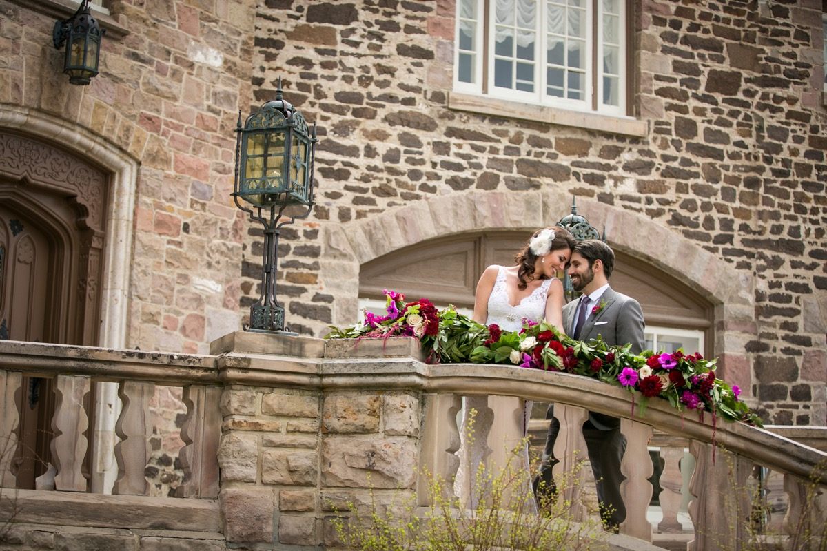 newlywed_couple_resting_heads_against_each_other_outside_brick_wedding_venue_on_balcony_classy_wedding_inspiration.jpg
