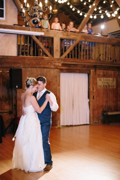 newlyweds_first_dance_in_barn_reception_guests_watching_overhead.jpg