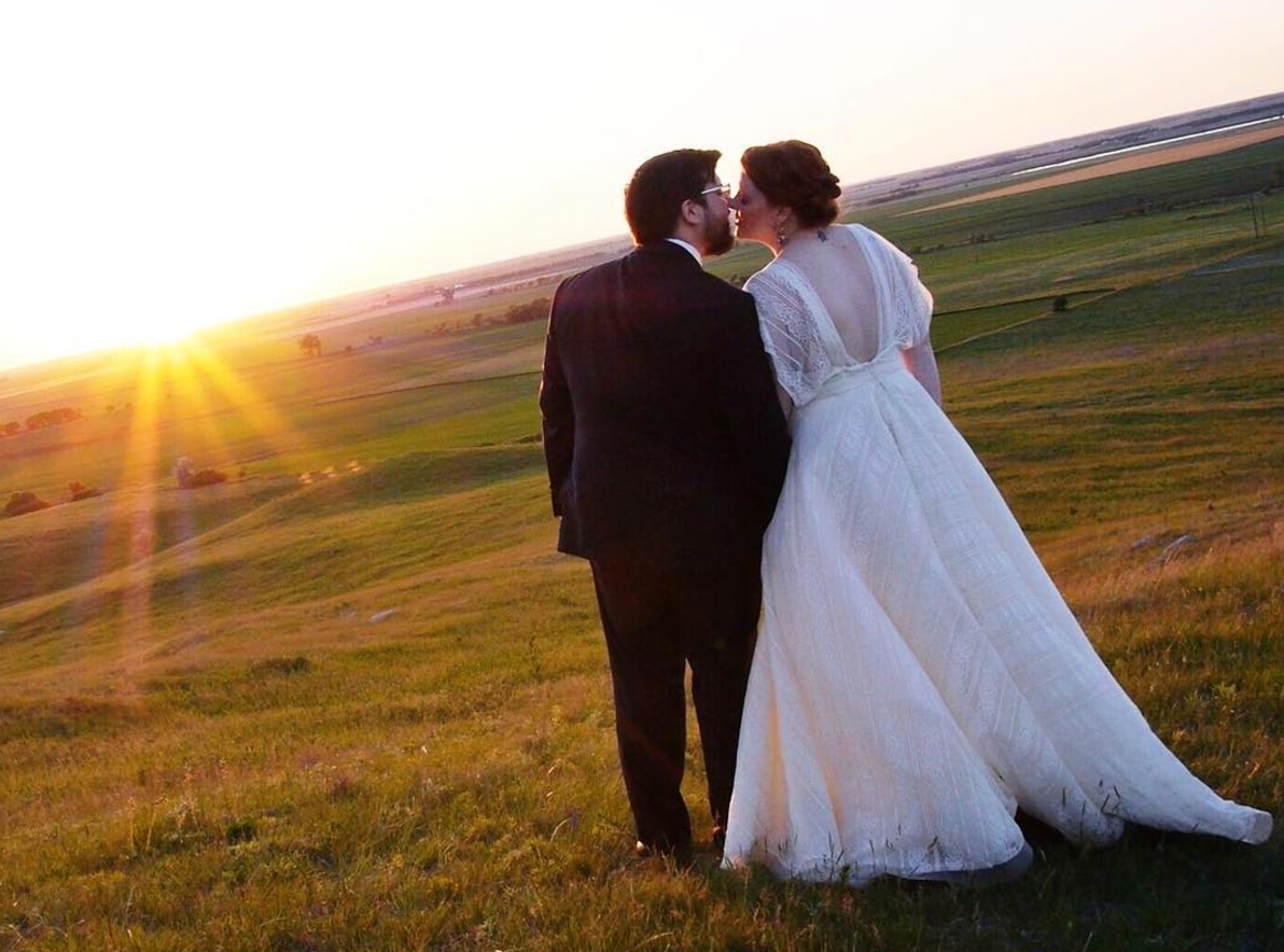 newlyweds_kissing_at_golden_hour_in_empty_minnesota_field_groom_wearing_glasses.png