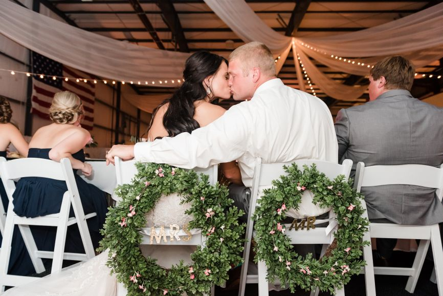 newlyweds_kissing_greenery_wreaths_airport_hangar_diy_wedding.jpg