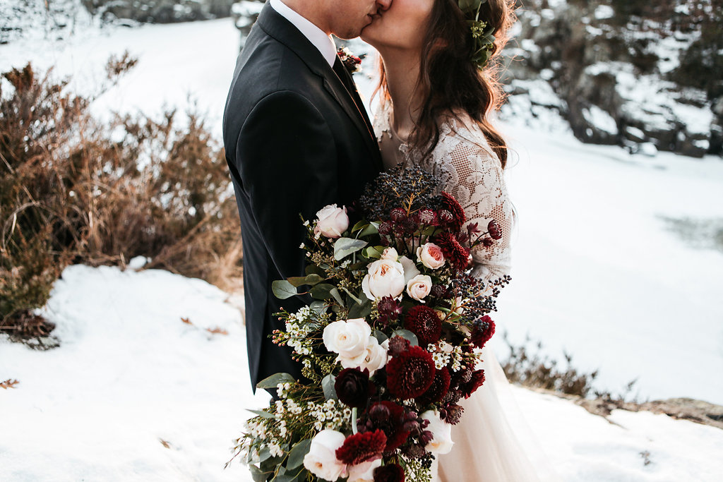 newlyweds_kissing_in_snow_giant_roses.jpg