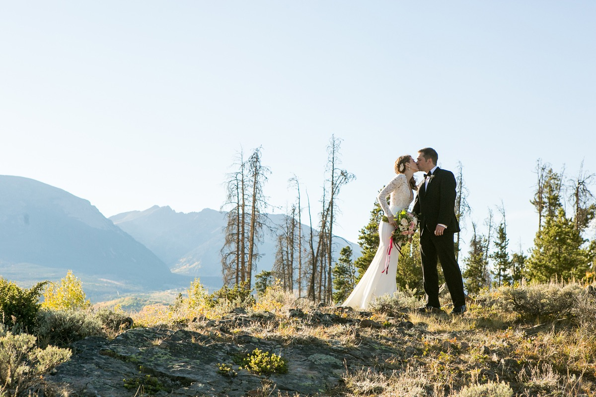 newlyweds_kissing_with_mountains_in_background_sunny_colorado.jpg