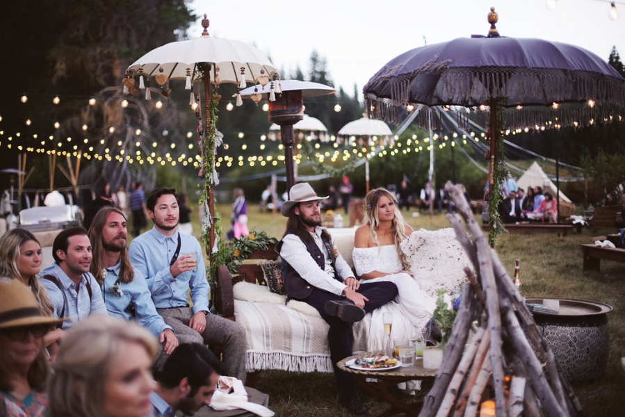 newlyweds_sitting_on_couch_rental_with_family_and_friends_outdoor_reception_with_tea_lights_and_bonfire.jpg