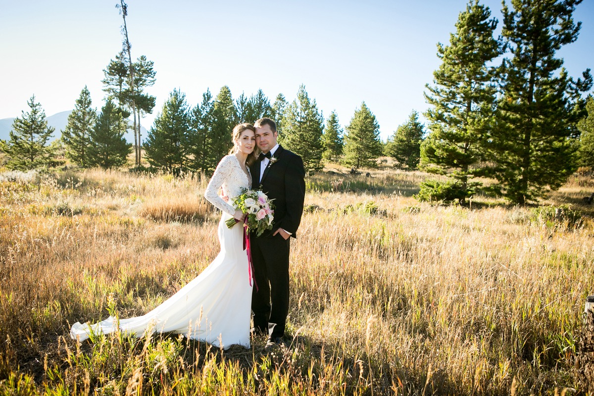newlyweds_standing_in_field_with_pine_trees_yellow_grass.jpg
