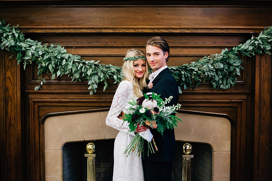 newlyweds_standing_in_front_of_fireplace_greenery_banner.jpg