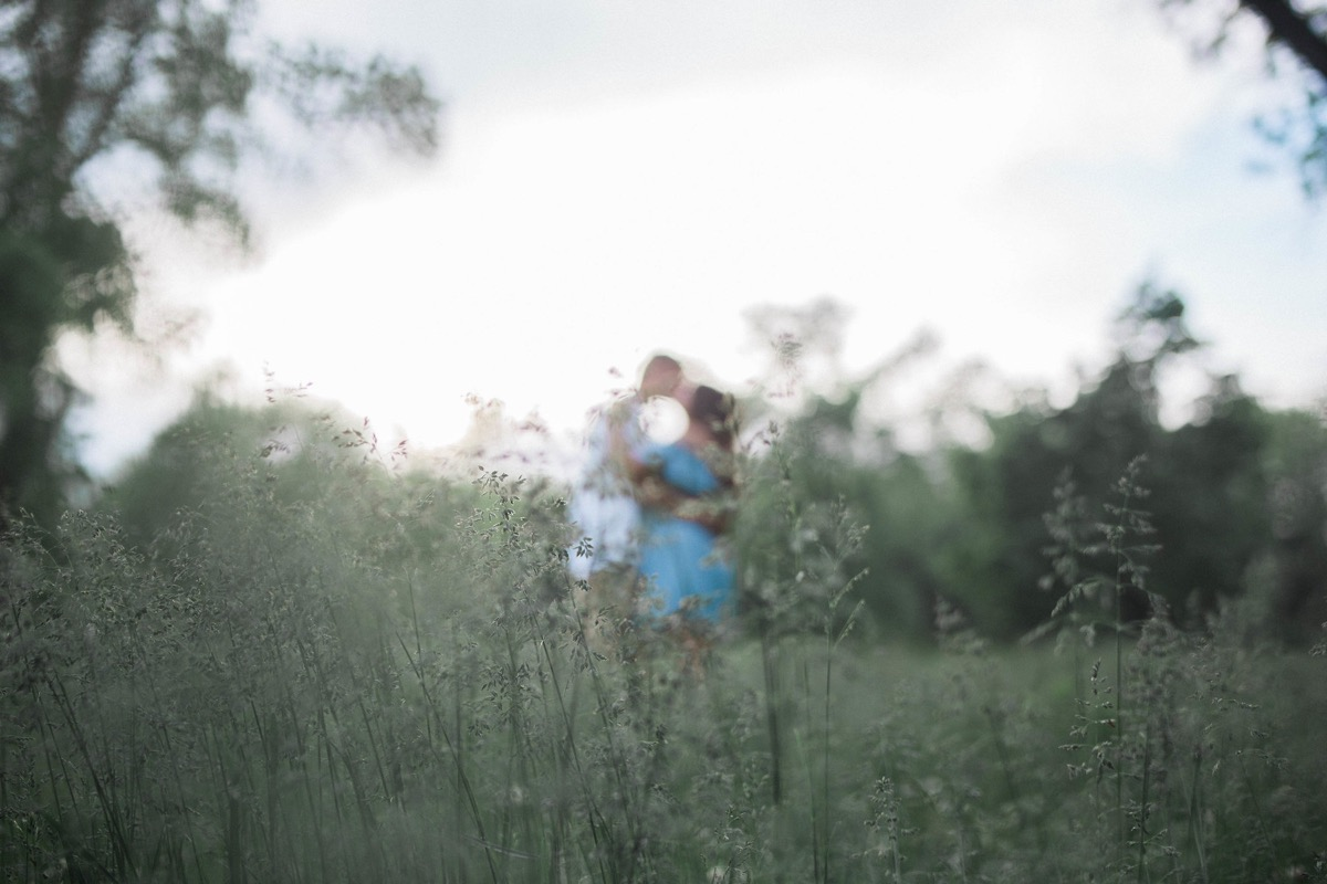 out_of_focus_blurry_engagement_photo_kissing_in_field.jpg