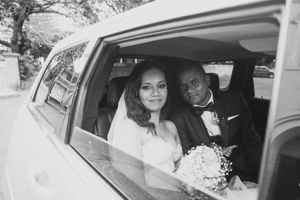 outside_picture_of_newlyweds_sitting_in_car.jpg