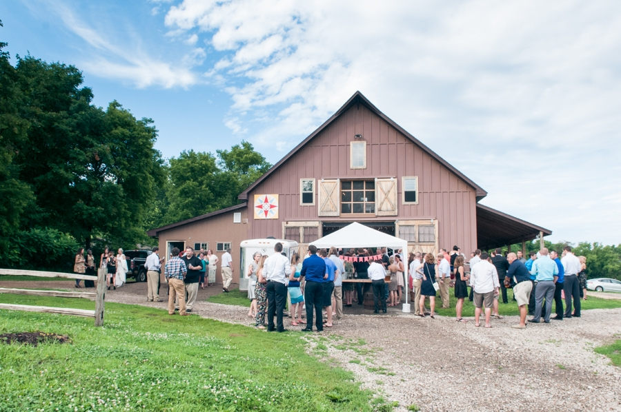 outside_view_of_brown_barn_wedding_guests_mingling.jpg