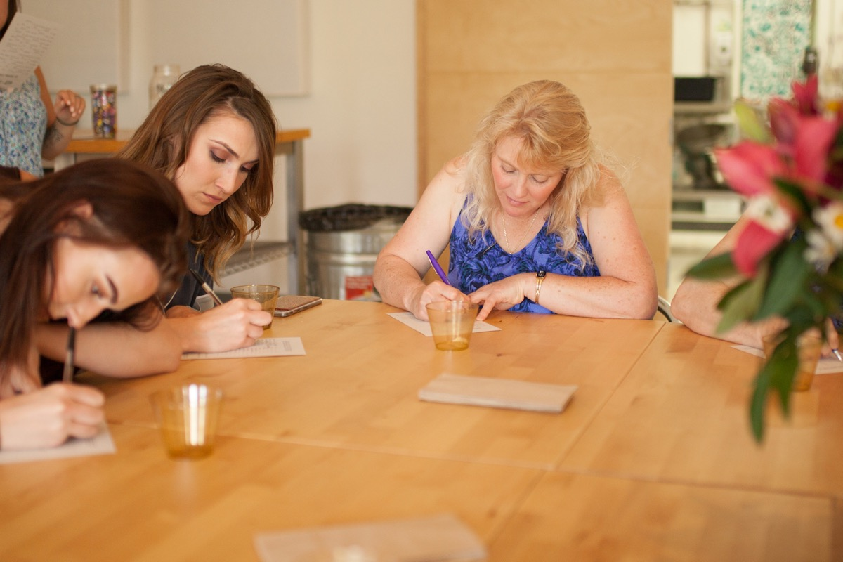 pajama_bridal_shower_guests_writing_game_on_table.jpg