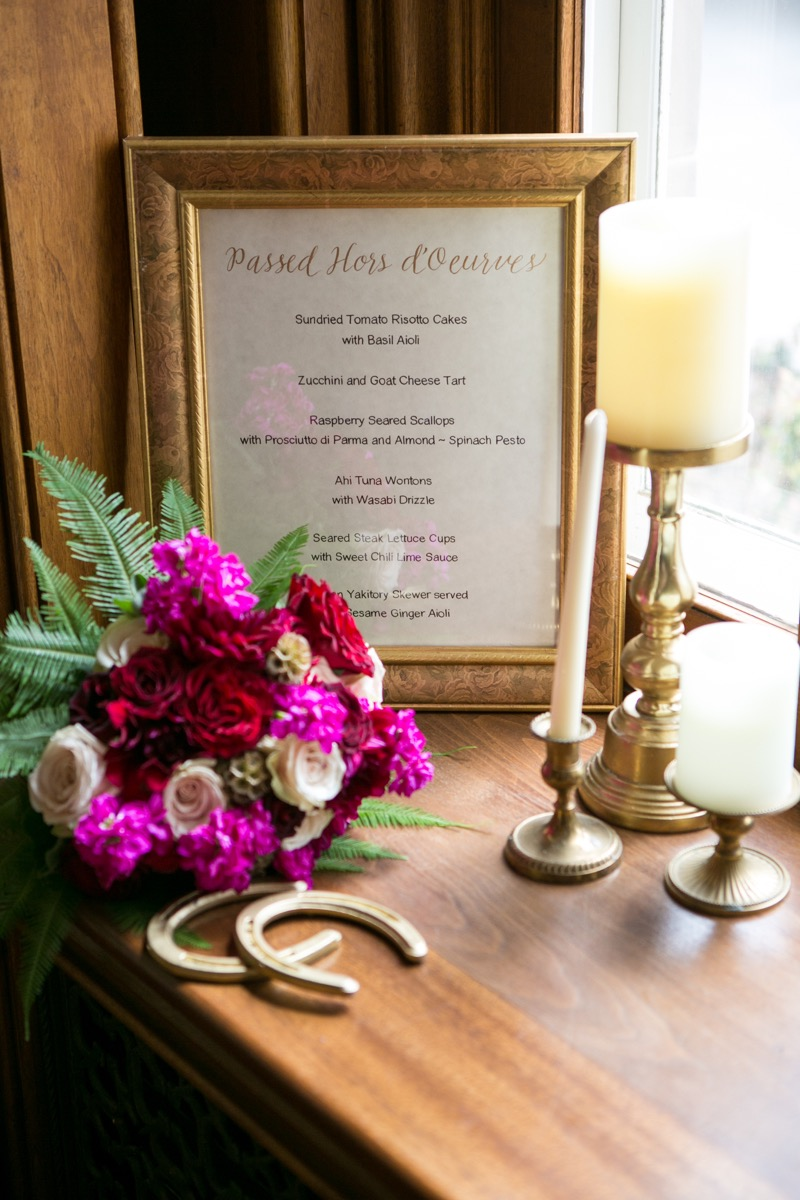 passed_hors_doeurves_sign_in_gold_frame_black_font_white_paper_next_to_gold_candle_holders_horse_shoes.jpg