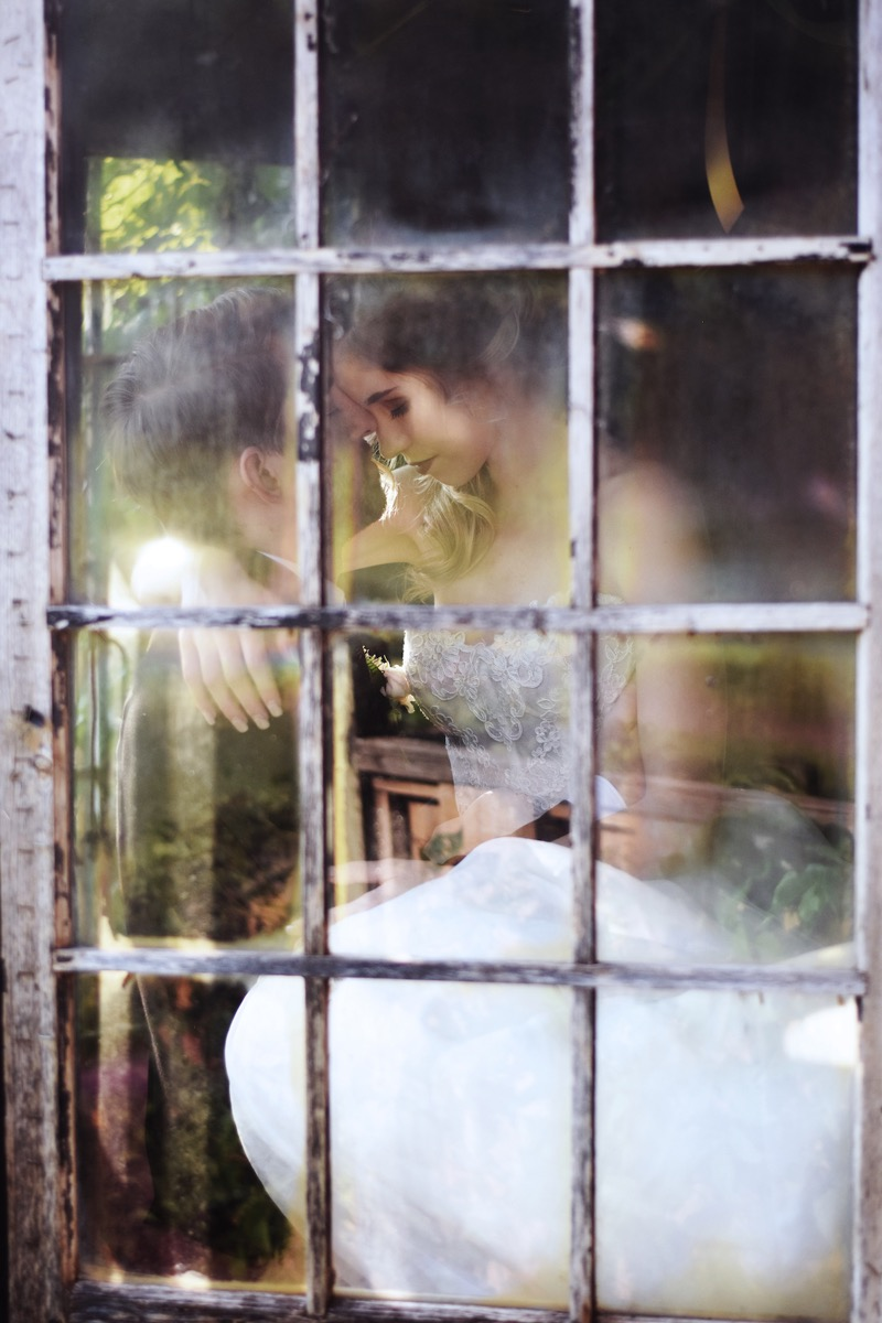 photo_looking_through_glass_window_wedding_couple_touching_foreheads.jpg