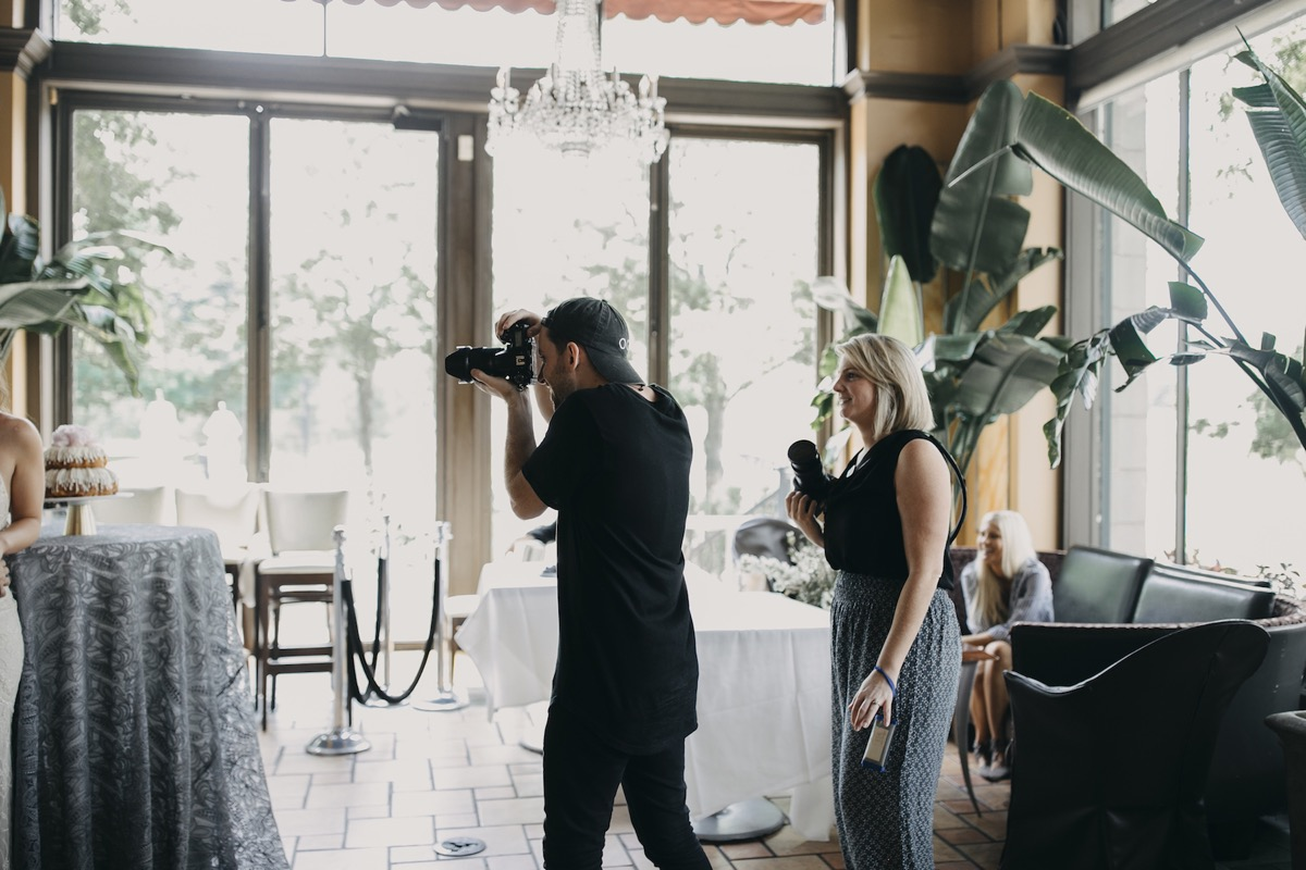 photographer_photographing_bride_and_groom_at_dessert_table.jpg
