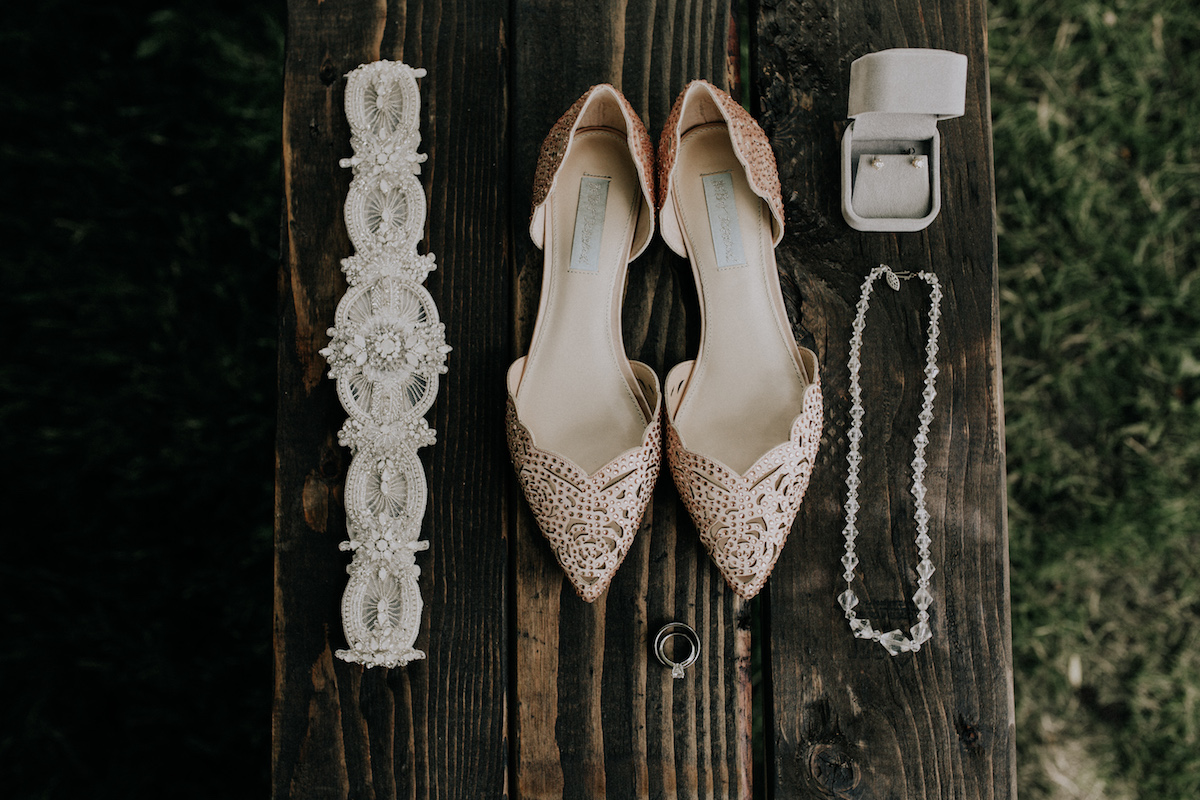 pretty_wedding_accessories_flatlay_on_dark_wood_bench.jpg