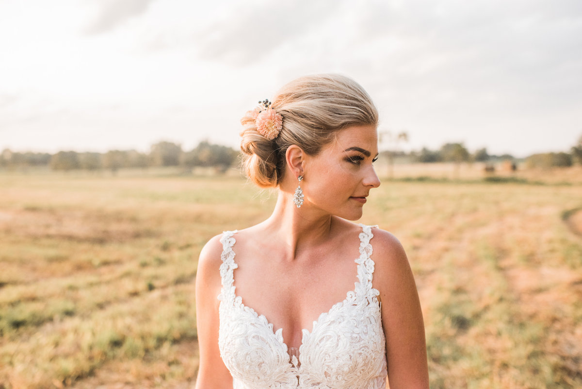 radiant_blonde_bride_in_green_field_at_sunset_looking_away.jpg