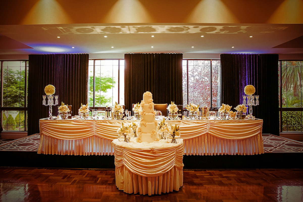reception_venue_wedding_party_table_and_tall_glamorous_wedding_cake.jpg