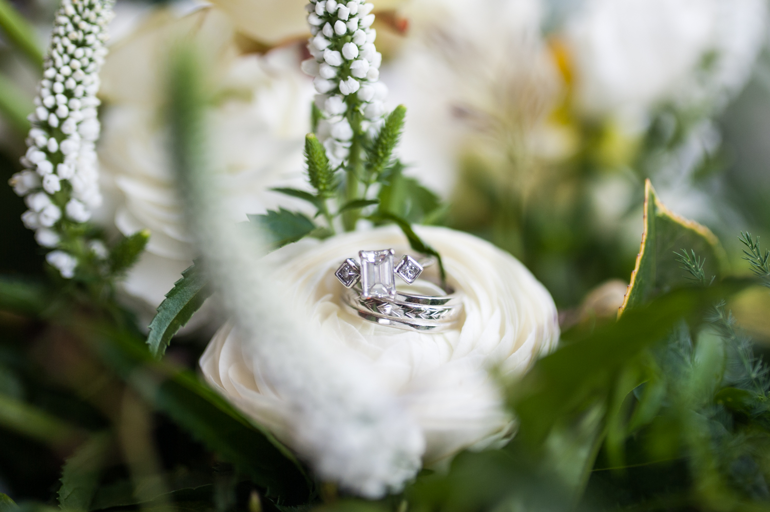 rectangle_diamond_wedding_ring_and_band_sitting_on_white_flowers_in_bouquet.jpeg